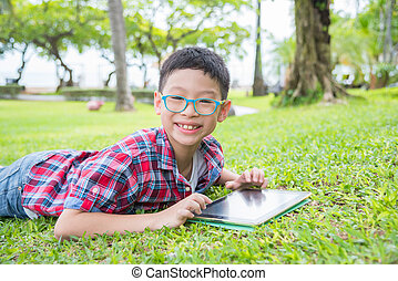 boy using tablet computer in park