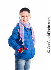 boy wearing blue jacket and scarf smiling over white background