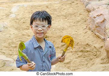 boy with shovel for digging in sandbox