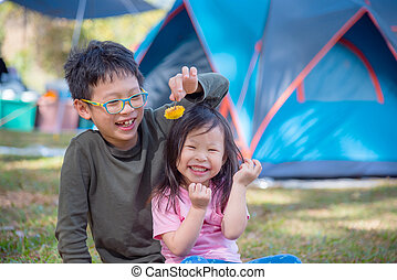 Young asian brother and sister playing together at camping