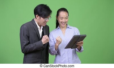 Young Asian business couple getting good news together -...