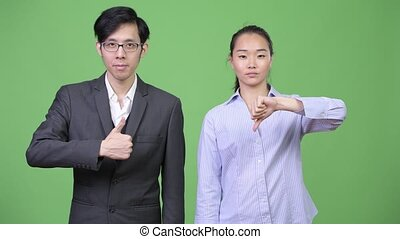Young Asian business couple having different decisions...