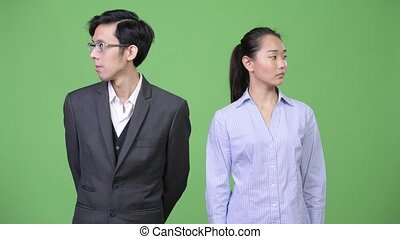 Young Asian business couple looking away together - Studio...