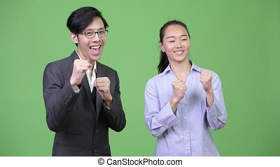 Young Asian business couple ready to fight together