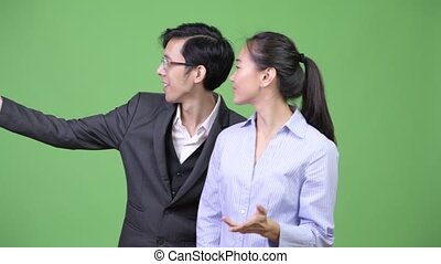 Young Asian business couple showing phone together