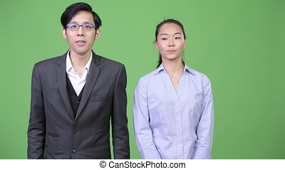 Young Asian business couple together - Studio shot of young...