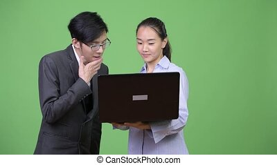 Young Asian business couple using laptop together