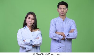 Young Asian business couple with arms crossed together