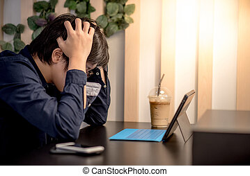 Young Asian business man feeling stressed while working in coffee shop