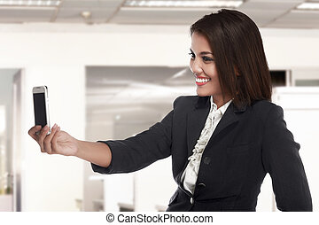 Young asian business woman in black suit taking selfie using smartphone