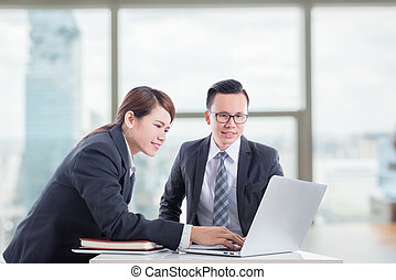 Young asian businessman and businesswoman discussing about work in office