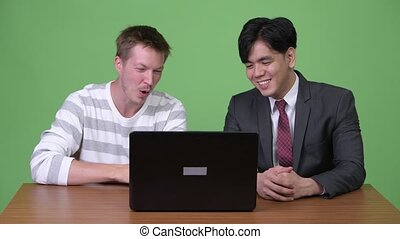 Young Asian businessman and young Scandinavian businessman working together with laptop