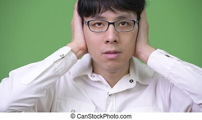 Young Asian businessman covering ears as hear no evil...