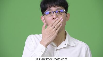 Young Asian businessman covering mouth and looking guilty -...