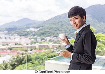 Young asian businessman drinking coffee. Standing at the terrace, looking and smile to camera