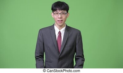 Young Asian businessman explaining while showing something to the back