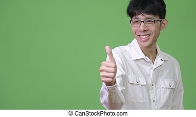 Young Asian businessman giving thumbs up