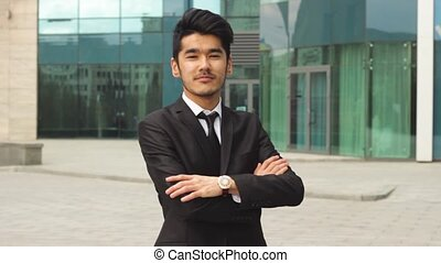 Young asian businessman looking in camera