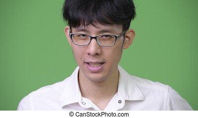 Young Asian businessman nodding head no - Studio shot of...