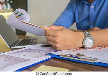 Young Asian businessman reading financial report document
