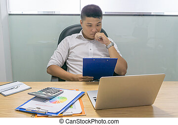 Asian businessman reading financial report document