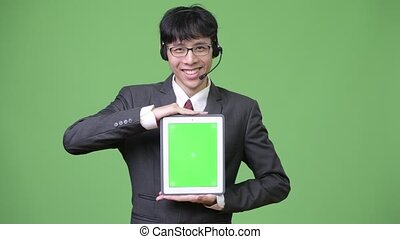 Young Asian businessman showing digital tablet to camera while working as call center representative
