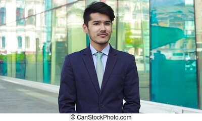 Young Asian businessman standing on street