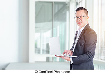 Young Asian businessman using tablet computer in office