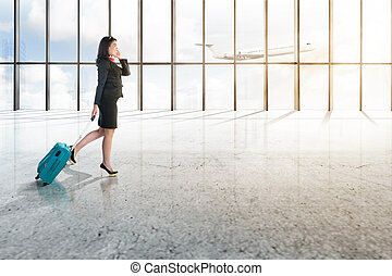 Young asian businessman with mobile phone and blue suitcase walking on the airport hall