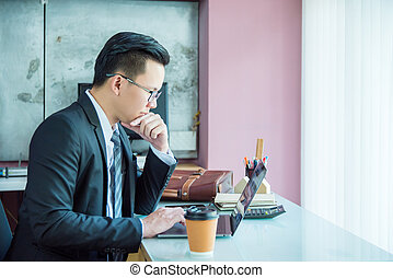 Young asian businessman working with laptop computer in office