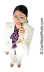 Young Asian businesswoman looking through a magnifying glass