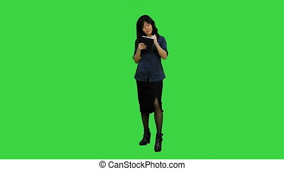 Young asian businesswoman making notes during interview on a Green Screen, Chroma Key
