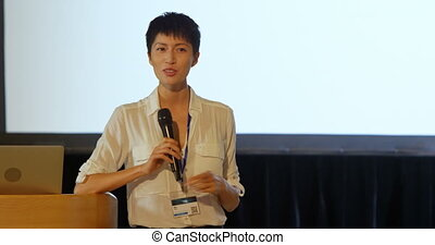 Front view of young Asian businesswoman speaking in speaker on stage in auditorium. She is smiling and standing at podium 4k