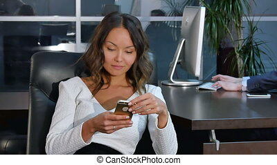Young asian businesswoman using mobile phone in office