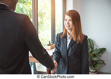 Young asian businesswoman wearing black suit shaking hand with partner in office