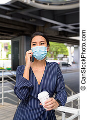 Young Asian businesswoman with mask talking on the phone while having coffee on the go as the new normal during covid-19