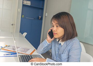 Asian businesswoman working on laptop and answer the phone call