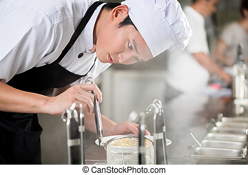 Young Asian chef plating food in a restaurant
