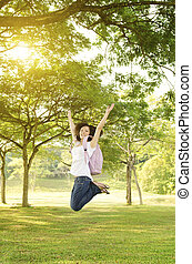 Young Asian college girl student open arms jumping