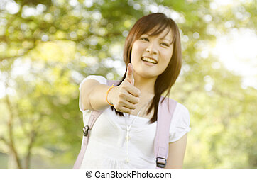 Young Asian college girl student thumb up