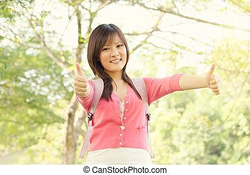 Young Asian college student showing thumb up