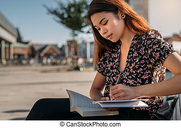 Young Asian college student studying outside on a campus bench