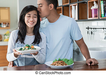 young asian couple at the kitchen cooking