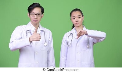 Young Asian couple doctors having different decisions...