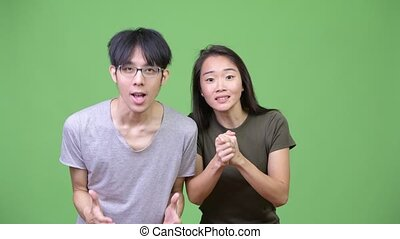 Young Asian couple getting good news together - Studio shot...