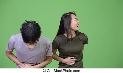 Young Asian couple having stomach ache together