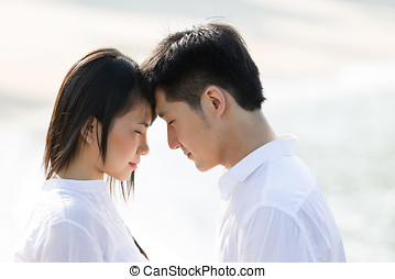 Young Asian couple on the beach - Portrait of a happy Asian...