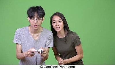 Young Asian couple playing games together