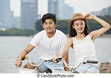 young asian couple riding bike in city park