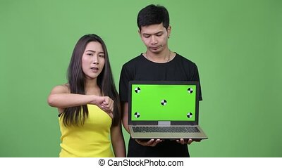 Young Asian couple showing laptop and giving thumbs down